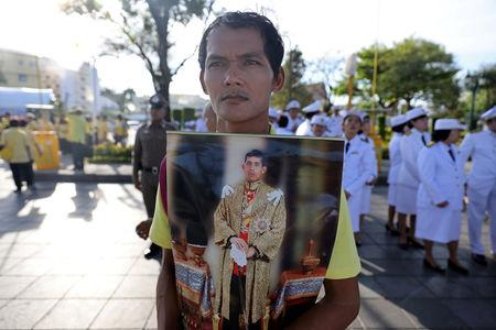 A man holds an image of King Maha Vajiralongkorn during his coronation in Bangkok, Thailand, May 4, 2019. REUTERS/Athit Perawongmetha