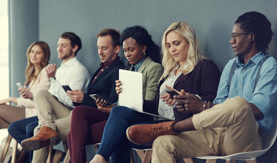 Shot of a group of businesspeople using different wireless devices while waiting in line for an interview