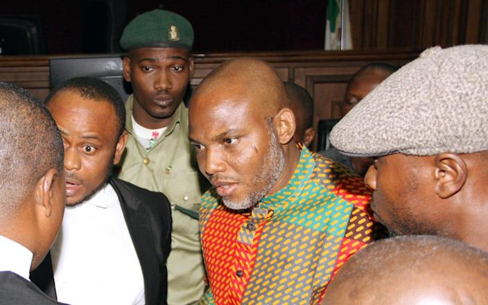 Biafran separatist leader Nnamdi Kanu, center, speaks to his lawyers at the Federal High court in Abuja, Nigeria Friday, Jan. 29, 2016 - AP