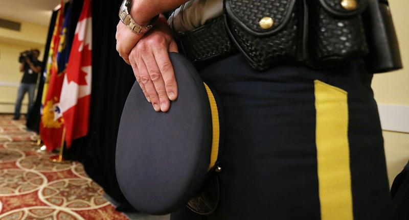 A Mountie holds his hat during a news conference. (Getty)