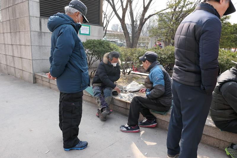 People at Jongmyo Park in Seoul, including two playing a game of Go.