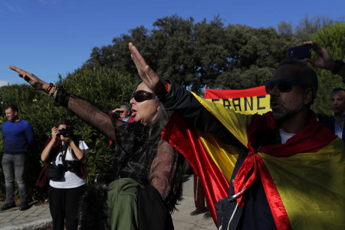 "People make the fascist salute as they gather outside Mingorrubio's cemetery, outskirts of Madrid, Thursday, Oct. 24, 2019. Forty-four years after his demise, the remains of Spanish dictator Gen. Francisco are to be dug out of his grandiose resting place outside Madrid and taken to a small family crypt, finally satisfying a long-standing demand of his victims' relatives and others who suffered under his regime. Inscription at ribbons reads in Spanish ""Barcelona always with Franco"". (AP Photo/Manu Fernandez)"