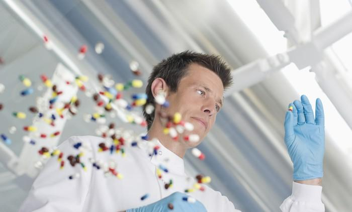 Scientist holding a pill with other pills on a clear surface.
