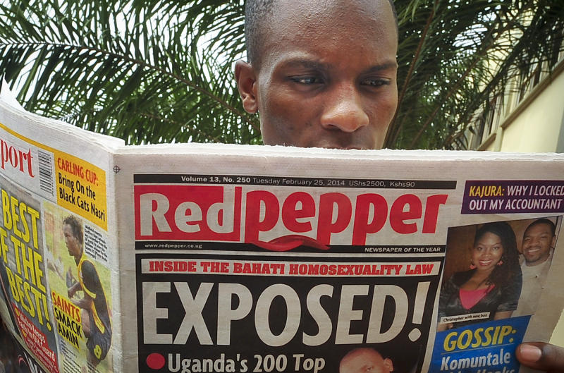 "A Ugandan reads a copy of the ""Red Pepper"" tabloid newspaper in Kampala, Uganda Tuesday, Feb. 25, 2014. The Ugandan newspaper published a list Tuesday of what it called the country's ""200 top"" homosexuals, outing some Ugandans who previously had not identified themselves as gay, one day after the president Yoweri Museveni enacted a harsh anti-gay law. (AP Photo/Stephen Wandera)"