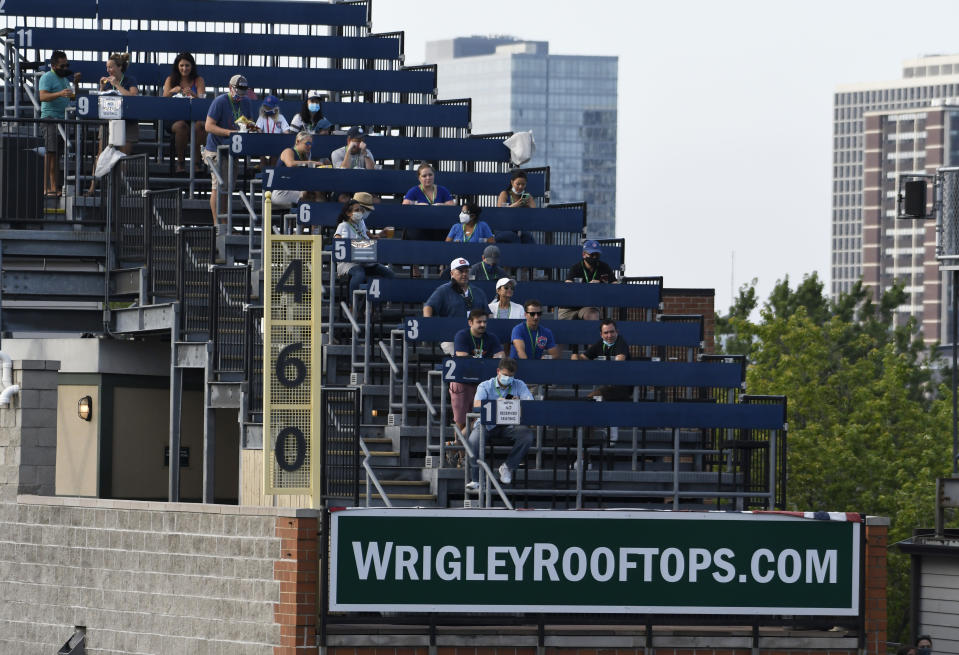 Fans watch from the rooftops an opening day baseball game between the Chicago Cubs and the Milwaukee Brewers, Friday, July, 24, 2020, in Chicago. (AP Photo/David Banks)
