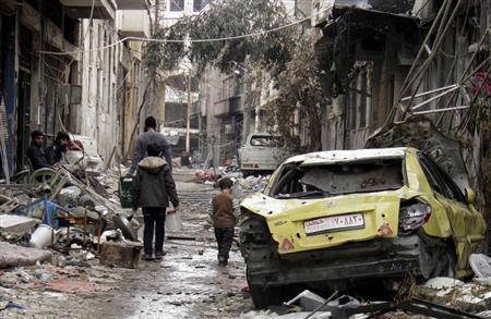 People walk past damaged car along a damaged street in the besieged area of Homs