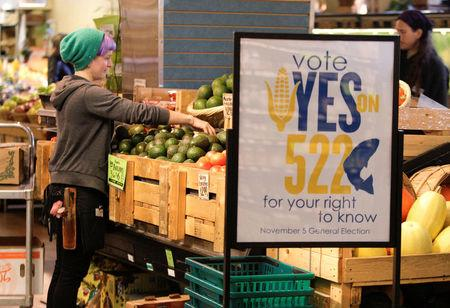 FILE PHOTO: An employee stocks produce near a sign supporting a ballot initiative in Washington state that would require labeling of foods containing genetically modified crops at the Central Co-op in Seattle, Washington October 29, 2013. REUTERS/Jason Redmond/File Photo