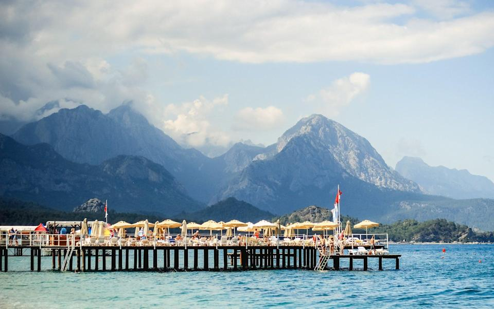 jetty into sea with yellow umbrellas, backed by mountains - Andrei Troitskiy /Moment RF