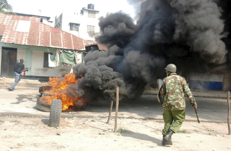 A riot police officer near to tyres on fire, lit by Muslim youths, outside Masjid Musa Mosque, in Majengo, Mombasa, Kenya, Tuesday, Aug. 28, 2012. Police and protesters fought running battles as a violent backlash to the killing of a radical Islamic preacher continued Tuesday in Kenya's second largest city city of Mombasa, which left several people hospitalized, a police and human rights official said. Police officers teargased rowdy youth on their second day of protests over the killing Monday of Aboud Rogo Mohammed, who was sanctioned by the U.S. government and the U.N. for his alleged connection to an al-Qaida-linked Somali militant group, al-Shabab, regional Police boss Aggrey Adoli said. (AP Photo)