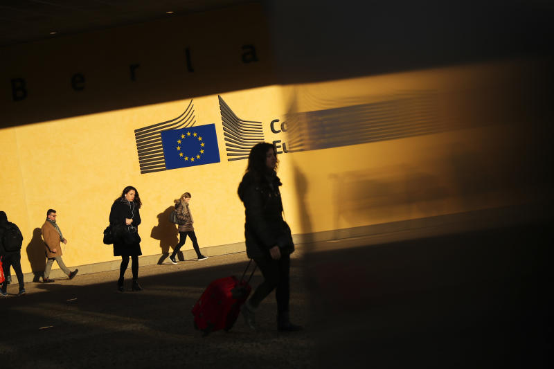 Commuters walk past the European Commission headquarters in Brussels, Monday, Feb. 11, 2019. European Union Brexit negotiator Michel Barnier is urging Britain's Prime Minister Theresa May to spell out how she plans to win over Parliament less than two months before Britain leaves. (AP Photo/Francisco Seco)