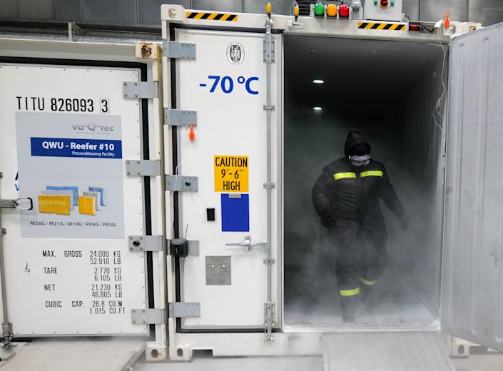 An employee of German logistic hardware producer va-Q-tec gets dry ice to fill an ultra-low temperature container to transport vaccination against the coronavirus disease (COVID-19) at the company's headquarters in Wuerzburg, Germany, November 18, 2020. REUTERS/Kai Pfaffenbach
