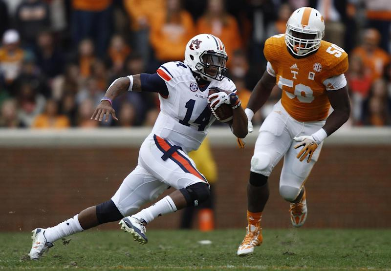 Auburn quarterback Nick Marshall (14) runs for yardage as Tennessee defensive lineman Corey Vereen (50) tries to catch him in the third quarter of an NCAA college football game on Saturday, Nov. 9, 2013, in Knoxville, Tenn. (AP Photo/Wade Payne)