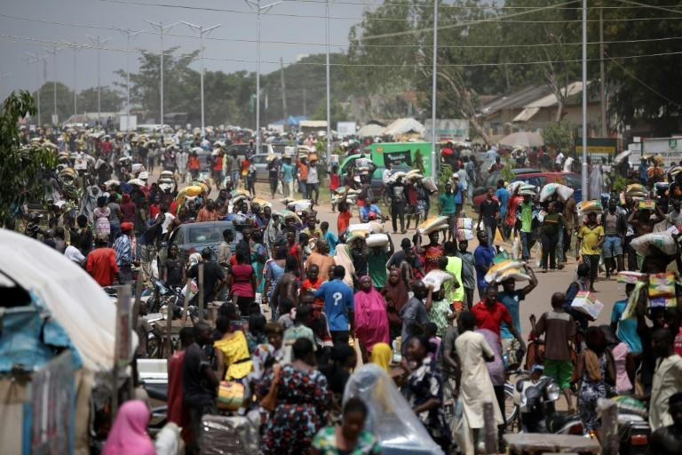 People carry bags of food on their heads after a warehouse is looted in Abuja, Nigeria in October last year