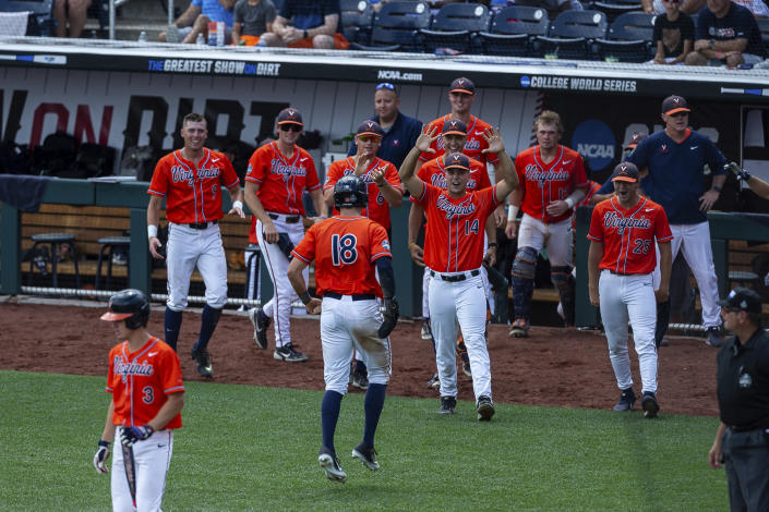 Virginia's Zach Gelof (18) celebrates his run with teammates in the seventh inning against Tennessee during a baseball game in the College World Series, Sunday, June 20, 2021, at TD Ameritrade Park in Omaha, Neb. (AP Photo/John Peterson)