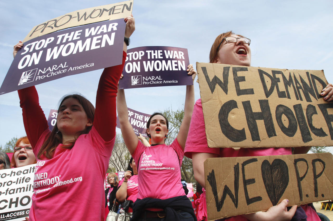 Erica Moses, 21, of Bethlehem, Pa., left, Rachel Graf Evans, 20, of Westtown Pa., and Hope Rehak, 21, of Chicago, take part in a rally in support of Planned Parenthood, Thursday, April 7, 2011, on the National Mall in Washington.