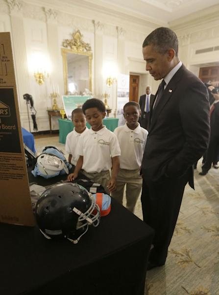 President Barack Obama listens to, from left, Alec Jackson, 8, Caleb Robinson, 8, and Evan Jackson, 10, all from McDonough, Georgia, as they explain their 'COOL PADS', a cooling system in football shoulder pads that keep players safe from overheating, Monday, April 22, 2013, at the White House Science Fair event in the State Dinning Room of the White House in Washington. (AP Photo/Pablo Martinez Monsivais)