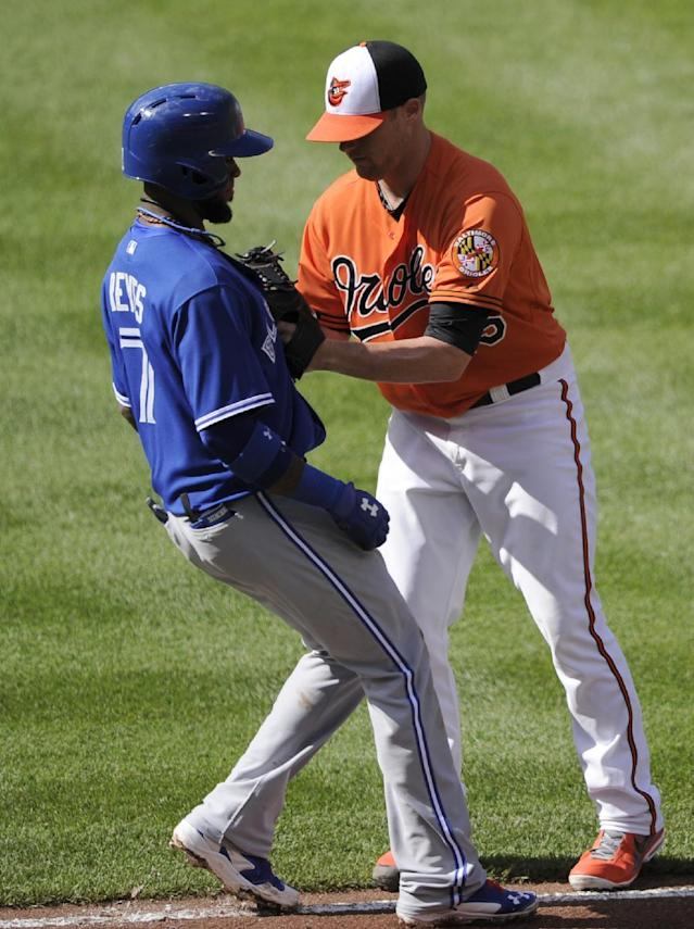 Toronto Blue Jays' Jose Reyes (7) is tagged out on a grounder, by Baltimore Orioles starting pitcher Bud Norris, right, during the second inning of a baseball game, Saturday, June 14, 2014, in Baltimore. (AP Photo/Nick Wass)