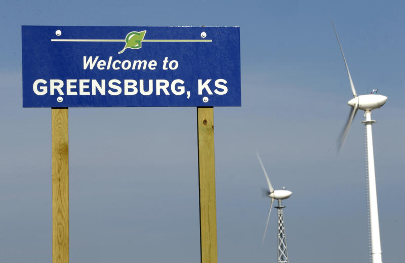 In this photo taken April, 18, 2014, wind turbines rise beyond a sign welcoming visitors to Greensburg, Kan. Seven years after an EF-5 tornado destroyed most of the community, Greensburg is one of the greenest towns in the country but struggles to regain residents that were displaced by the disaster. (AP Photo/Charlie Riedel)