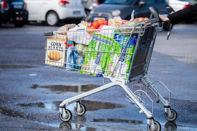 13 March 2020, Bavaria, Pullach: A customer pushes a shopping trolley filled to the brim across the parking lot of a supermarket. Photo: Matthias Balk/dpa (Photo by Matthias Balk/picture alliance via Getty Images)