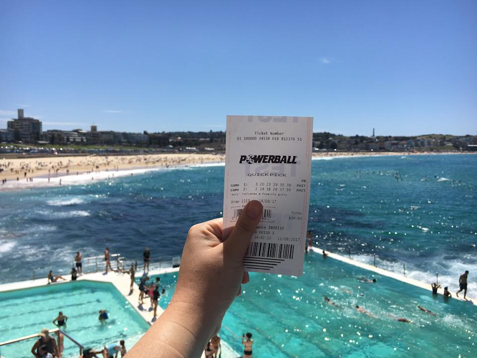 A person holds up a Powerball ticket with Sydney's Bondi Beach in the background.