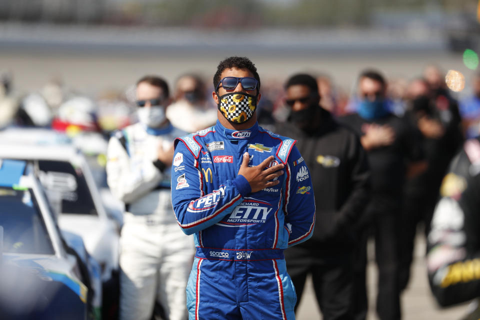 Bubba Wallace stands for the national anthem before a NASCAR Cup Series auto race at Michigan International Speedway in Brooklyn, Mich., Saturday, Aug. 8, 2020. (AP Photo/Paul Sancya)