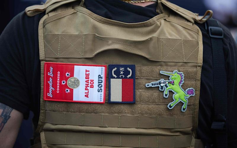 In this file photo a member of the far-right militia, Boogaloo Bois, walks next to protestors demonstrating outside Charlotte Mecklenburg Police Department Metro Division 2 just outside of downtown Charlotte, North Carolina, on May 29, 2020 - Logan Cyrus/AFP/Getty