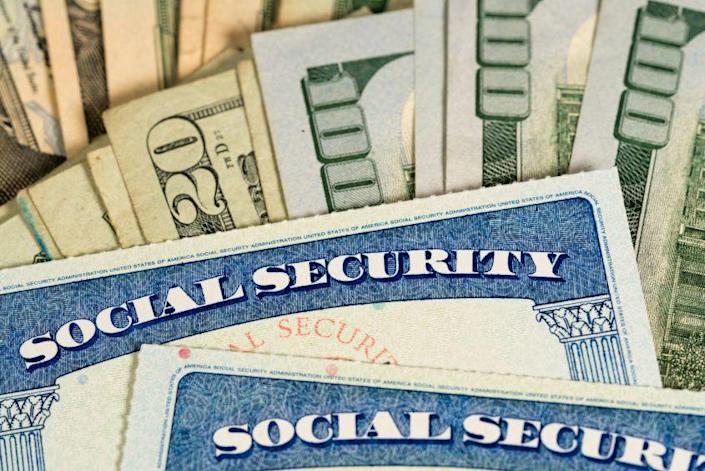 Concept art showing Social Security cards on top of a stack of cash.