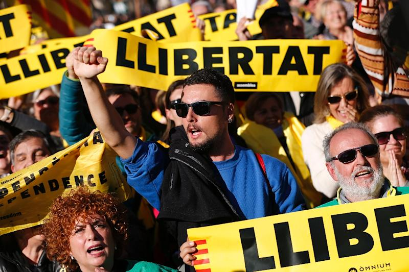 """People hold placards reading """"Freedom"""" outside Catalan's parliament during its inaugural session on January 17, 2018 in Barcelona"""