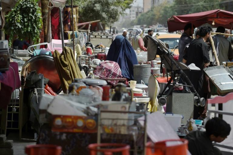 Buyers browse second-hand household items for sale at a market in the northwest neighbourhood of Khair Khana in Kabul (AFP/WAKIL KOHSAR)