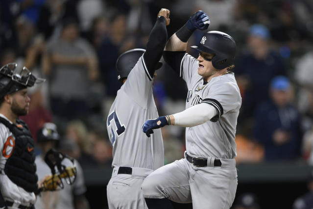 New York Yankees' Clint Frazier, right, celebrates his three-run home run with Aaron Hicks, center, as Baltimore Orioles catcher Austin Wynns stands at left during the fifth inning of a baseball game Tuesday, May 21, 2019, in Baltimore. (AP Photo/Nick Wass)