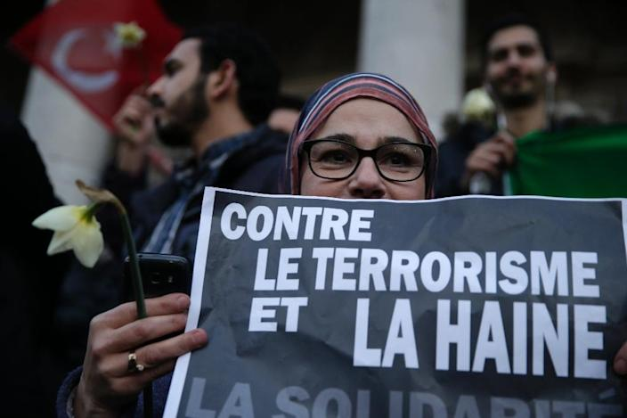 """A woman holds a sign reading """"Against terrorism and hatred, Solidarity"""" as people gather at a makeshift memorial on the Place de la Bourse (Beursplein) in Brussels on March 23, 2016 (AFP Photo/Kenzo Tribouillard)"""