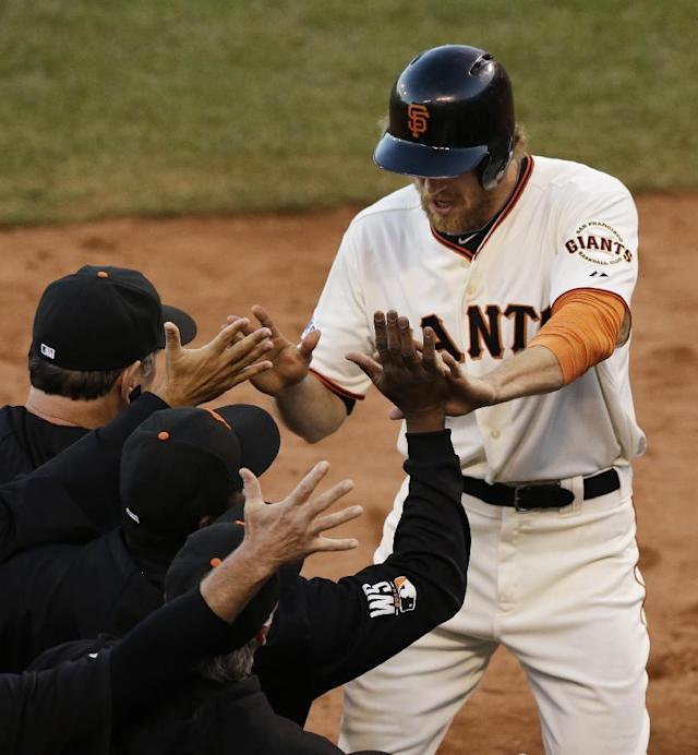 San Francisco Giants Hunter Pence is congratulated by teammates after scoring on an RBI ground out by Brandon Crawford during the second inning of Game 5 of baseball's World Series against the Kansas City Royals Sunday, Oct. 26, 2014, in San Francisco. (AP Photo/Jeff Chiu)
