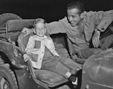 <p>Humphrey Bogart smiles as his and Lauren Bacall's son, Stephen, visits the set of his film <em>Battle Circus </em>in 1953. </p>