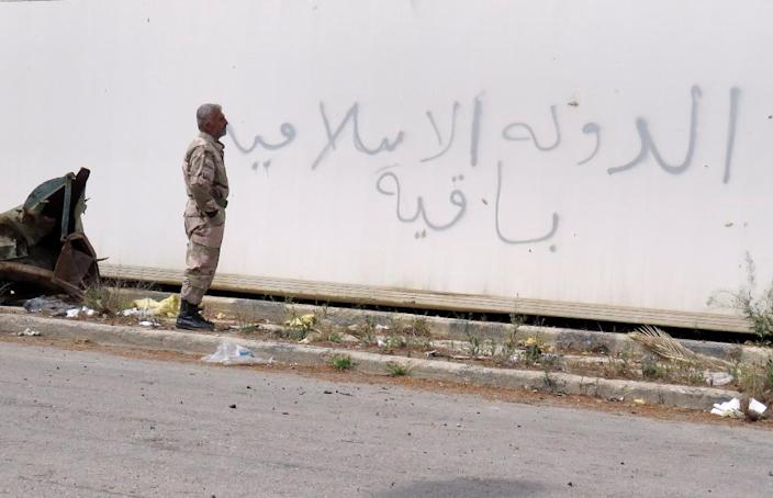 """A Syrian soldier looks at graffiti reading in Arabic, """"The Islamic State is staying"""", in the historical city of Palmyra in central Syria on March 29, 2016 (AFP Photo/)"""