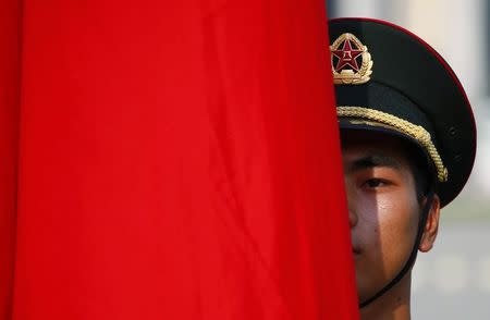 An honour guard member is seen behind a red flag during a welcoming ceremony for Kuwait's Prime Minister Sheikh Jaber al-Mubarak al-Sabah at the Great Hall of the People in Beijing
