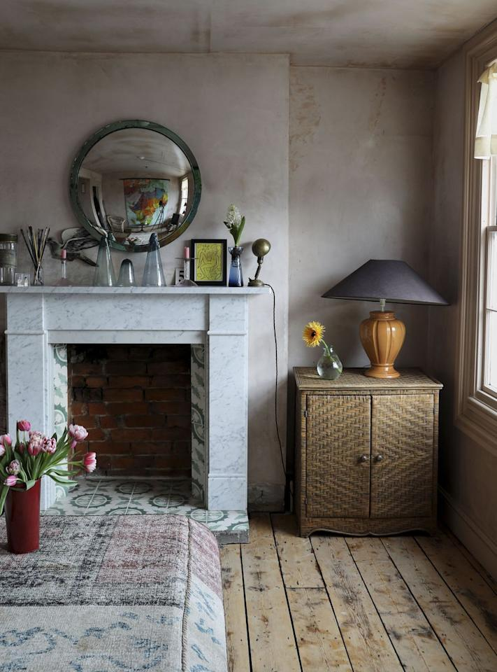 """<p>""""Before it was trendy, or we had all these amazing plaster effect paints that are now available, I fell in love with the colour of plaster. Because it appeared all over the house, I decided to get my builders to stop once all the walls and ceiling were plastered and to just seal it. At the time they thought I was mad! </p><p>""""I then created my own colour to sit on all the woodwork, creating a super calm and inviting environment. I added the marble fireplace and the French tiles. The frill curtains are again available from Côte de Folk. The 1960s Heals convex mirror was found in a local antique shop and the rattan cupboard was a great find in Rye for £30.""""</p>"""