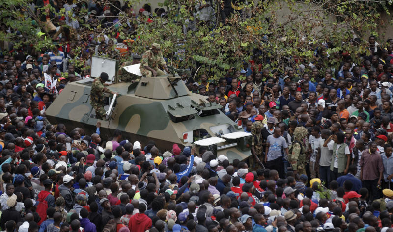 An army armored personnel carrier drives slowly through the gathered crowd of thousands demanding President Robert Mugabe stand down, on the road leading to State House in Harare, Zimbabwe Saturday, Nov. 18, 2017. In a euphoric gathering that just days ago would have drawn a police crackdown, crowds marched through Zimbabwe's capital on Saturday to demand the departure of President Robert Mugabe, one of Africa's last remaining liberation leaders, after nearly four decades in power. (AP Photo/Ben Curtis)