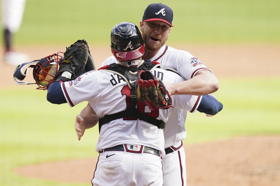 Atlanta Braves closer Will Smith (51) celebrates with Atlanta Braves catcher Travis d'Arnaud (16) embrace after the ninth inning of Game 3 of a baseball National League Division Series against the Milwaukee Brewers, Monday, Oct. 11, 2021, in Atlanta. The Atlanta Braves won 3-0. (AP Photo/Brynn Anderson)