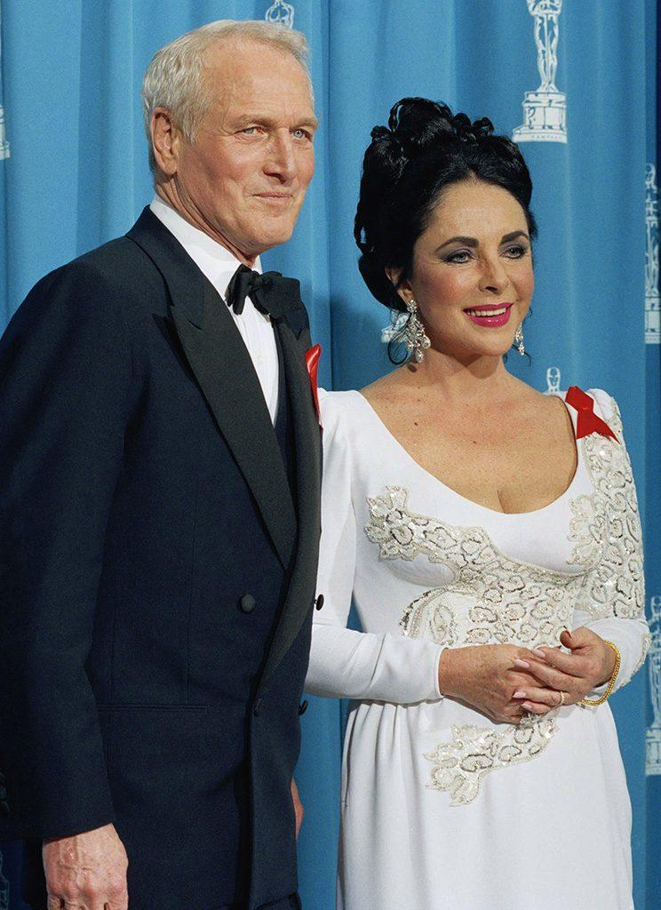 Elizabeth Taylor (with Paul Newman) proudly wore a red ribbon for AIDS awareness at the 64th Annual Academy Awards in 1992. (Photo: AP Photo/Bob Galbraith)