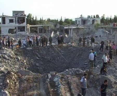 People gather around a crater in Homs city June 20, 2014, in this picture released by Syria's national news agency SANA. REUTERS/SANA/Handout via Reuters