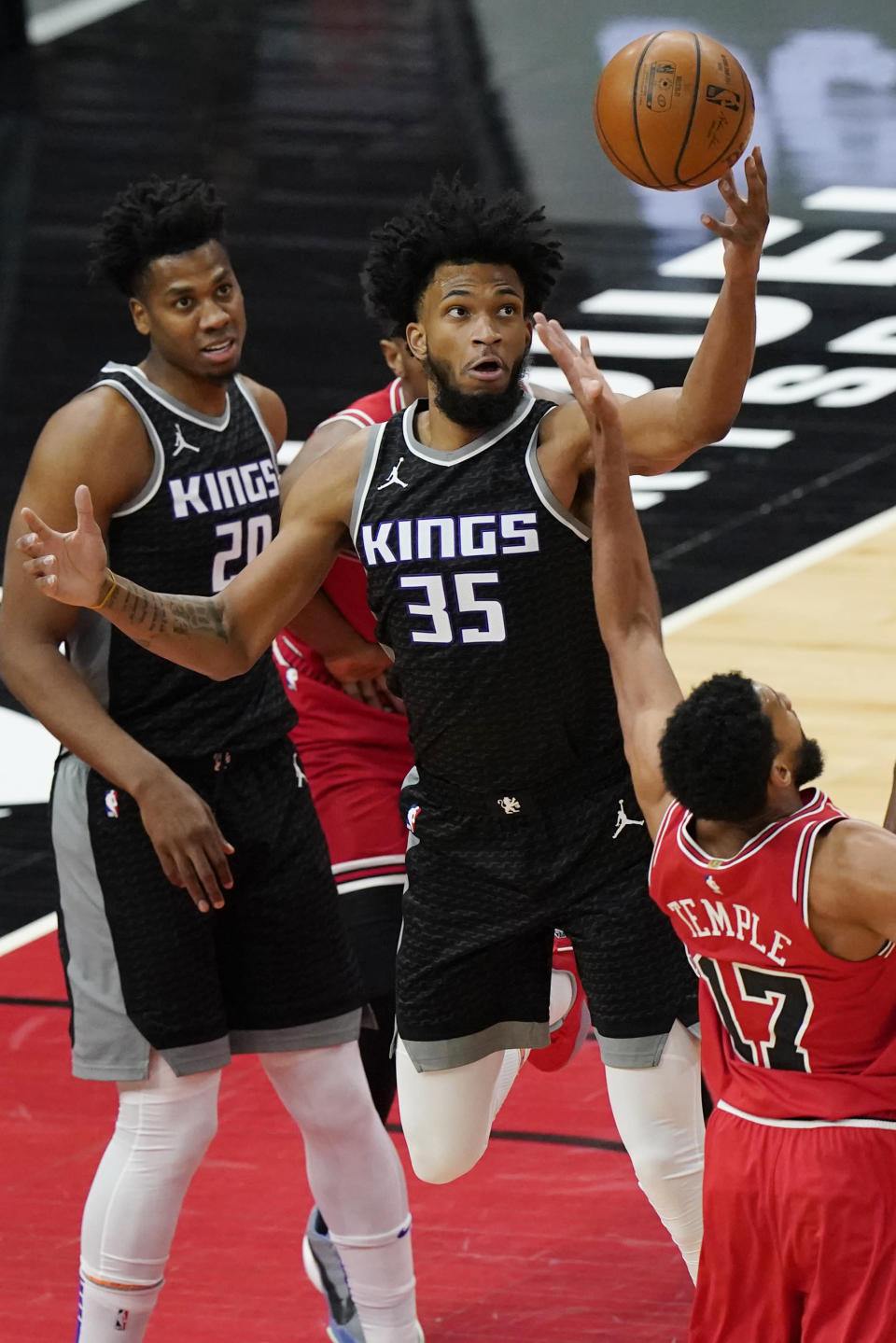 Sacramento Kings forward Marvin Bagley III (35) rebounds the ball against Chicago Bulls guard Garrett Temple as Sacramento Kings center Hassan Whiteside, left, watches during the first half of an NBA basketball game in Chicago, Saturday, Feb. 20, 2021. (AP Photo/Nam Y. Huh)