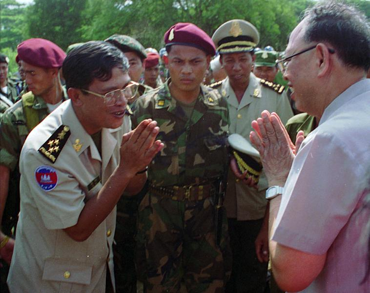FILE - In this Oct. 22, 1996 file photo, Cambodian then Deputy Prime Minister Hun Sen, left, says good-bye to Ieng Sary, a leader of Khmer Rouge dissidents, right, after he visited the former Khmer Rouge stronghold of Pailin, Cambodia. Ieng Sary, who co-founded Cambodia's brutal Khmer Rouge movement in 1970s, served as its public face abroad and decades later became one of its few leaders to face justice for the deaths of well over a million people, died Thursday, March 14, 2013. He was 87. (AP Photo/Ou Neakiry, File)