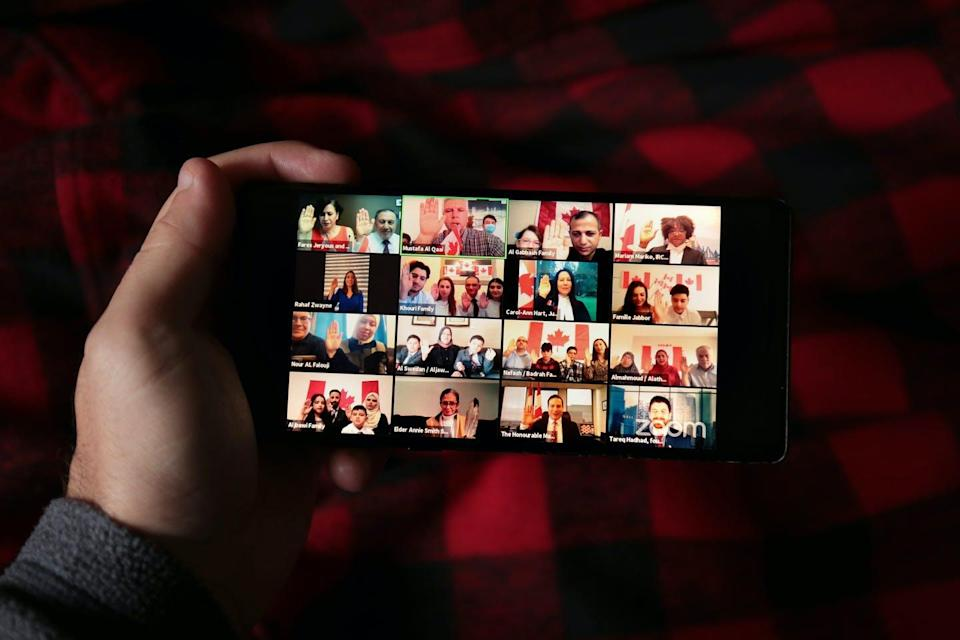 A man holds up a phone that shows a screen of many people taking part in the citizenship ceremony.