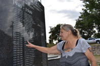 """Dana Amon finds the name of her stepfather who fought in World War II on a monument at Veterans Memorial Park, Aug. 25, 2021, in Watford City, N.D. Amon, who grew up in a double-wide trailer on a farm on the edge of the county seat, Watford City, remembers riding her horse across fields now dotted with tracts of modest housing lit up at night by the flares from nearby oil wells. """"Our little town just blew up at the seams,"""" she said. (AP Photo/Matthew Brown)"""