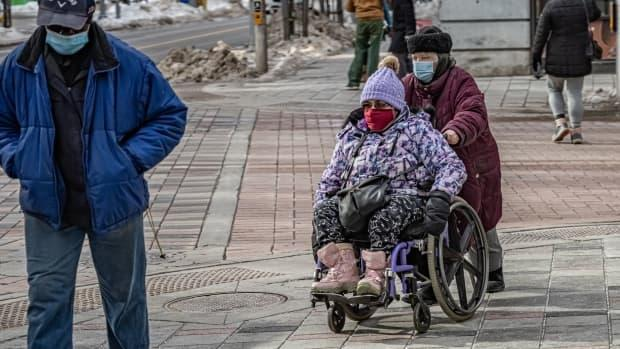 A wheelchair user in a mask makes their way across Bank Street in downtown Ottawa in early March 2021. On Thursday, health officials reported 83 new cases of the COVID-19 virus.  (Brian Morris/CBC - image credit)