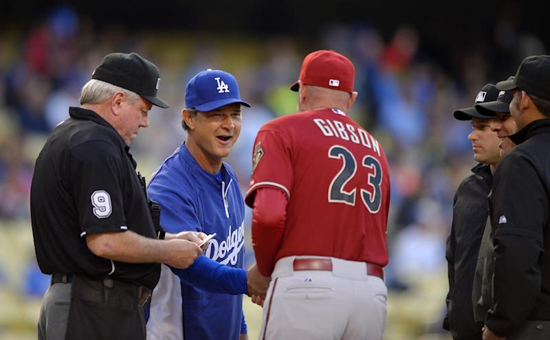 Los Angeles Dodgers manager Don Mattingly, second from left, and Arizona Diamondbacks manager Kirk Gibson shake hands as umpires watch prior to their baseball game, Wednesday, June 12, 2013, in Los Angeles. (AP Photo/Mark J. Terrill)