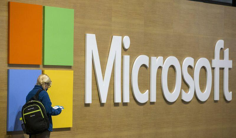 An attendee at the Microsoft Ignite technology conference is seen next to the Microsoft logo in Chicago