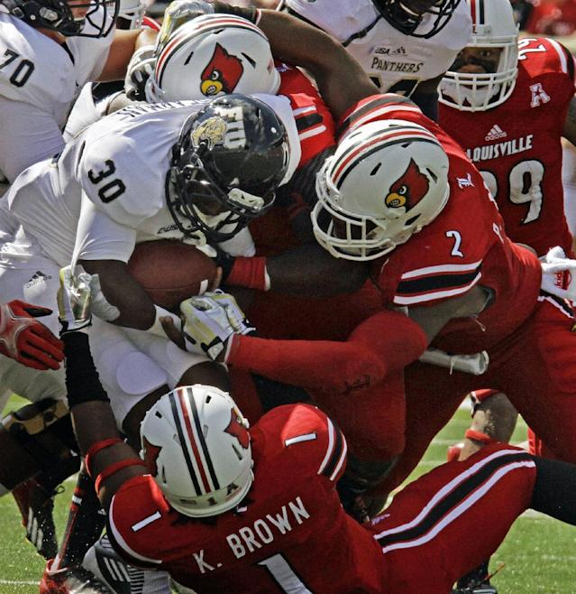 Louisville defenders Keith Brown (1), Jamaine Brooks (7) and Sheldon Rankins (98) swallow up Florida International runner Silas Spearman (30) during the first half run of an NCAA college football game in Louisville, Ky., Saturday, Sept, 21, 2013. (AP Photo/Garry Jones)