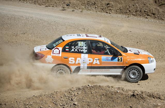 Iranian driver Hossein Ghodsi and his Iranian co-driver Arash Ramin Yekta (seen in the picture) of Saipa team drive their Kia Rio during the FIA Middle East Rally Championship (MERC) candidate event near the Iranian city of Shiraz on September 25, 2014. The MERC event in Shiraz was cancelled on September 26, 2014 after co-driver Arash Ramin Yekta died when the car rolled several times after taking a jump, said a member the organization who wished to remain anonymous. AFP PHOTO/BEHROUZ MEHRI (AFP Photo/BEHROUZ MEHRI)