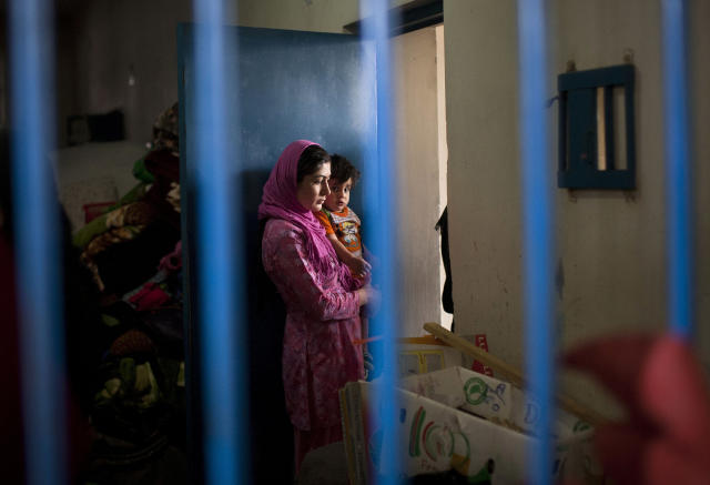 "Picture taken March 28, 2013 shows an Afghan female prisoner with her child inside her prison tract in Badam Bagh, Afghanistan's central women's prison, in Kabul, Afghanistan. 202 women living in the six- year- old jail, the majority of the women are serving sentences of up to seven years for leaving their husbands, refusing to accept a marriage arranged by their parents, or choosing to leave their parent's home with a man of their choice, all so-called ""moral"" crimes(. AP Photo/Anja Niedringhaus)"